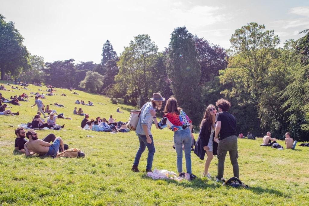 Junge Franzosen begrüßen sich auf einer Wiese mit Küsschen