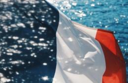 Wehende Frankreich-Flagge, im Hintergrund Meer