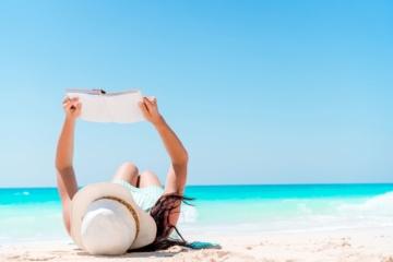 Frau liegt auf weißem Sandstrand und liest ein Buch