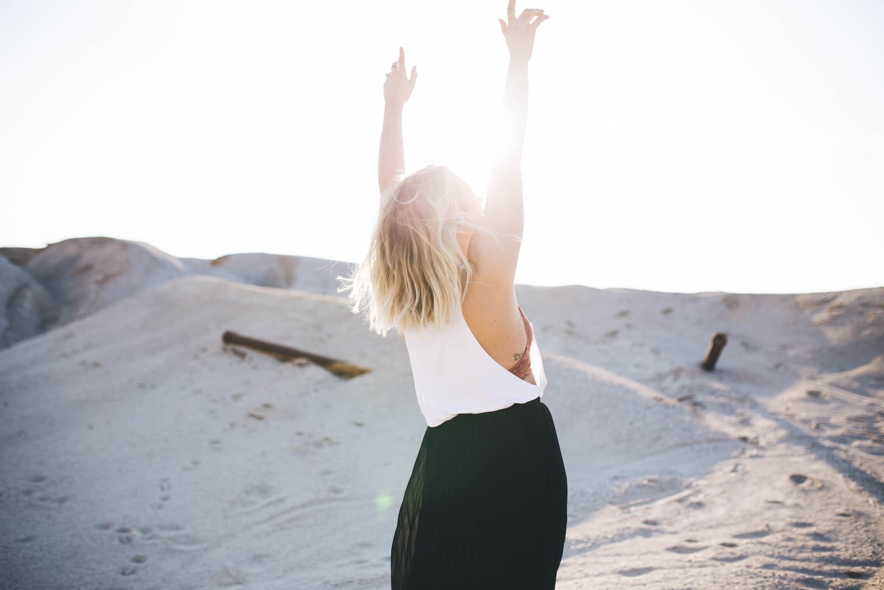 Frau steht am Strand und streckt die Arme in die Luft