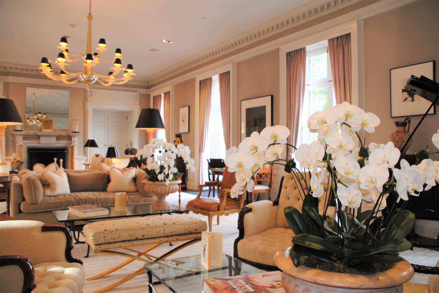 Gemütlich eingerichteter Wohnraum mit hellen Sofas und Blumen in der Glenmere Mansion
