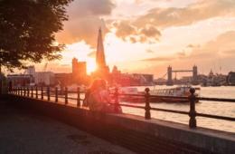 Zwei Freundinnen sitzen anders Themse in London bei Sonnenuntergang und freuen sich aufs Wochenende