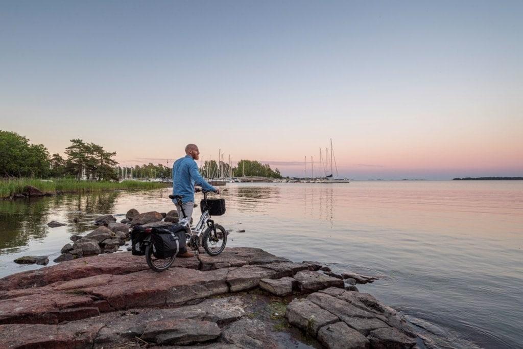 Mann steht mit seinem Fahrrad am See und blickt in die Weite