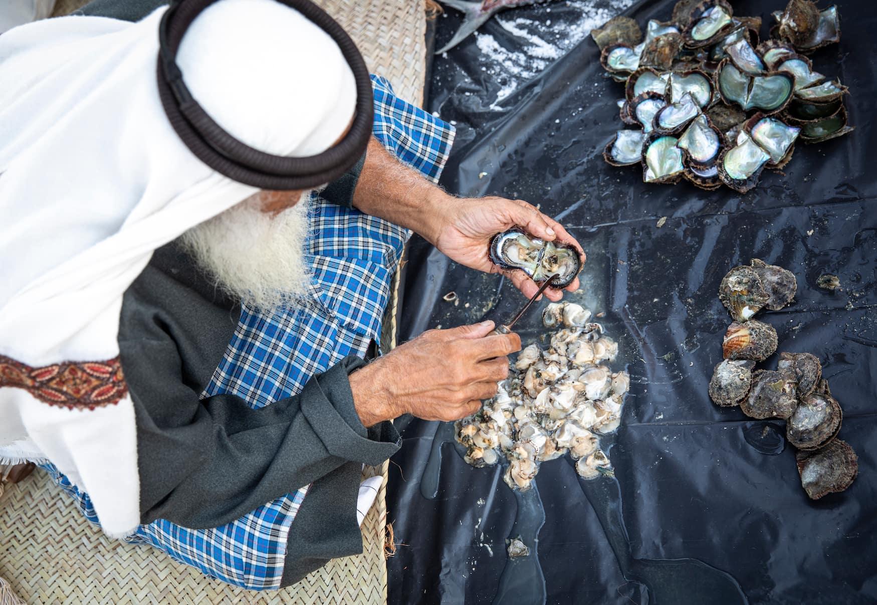 Mann öffnet Austern und Sicht Perlen am Hafen von Abu Dhabi