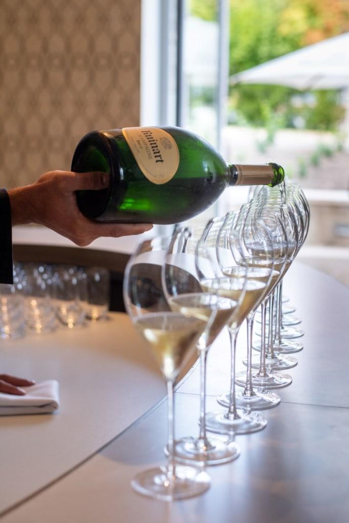 Jemand schüttet Ruinart-Champagne in Gläser
