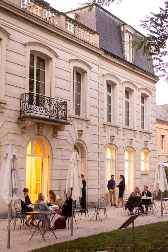 Auf einer Terrasse eines Landhauses in der Champagne sitzen und stehen Gäste