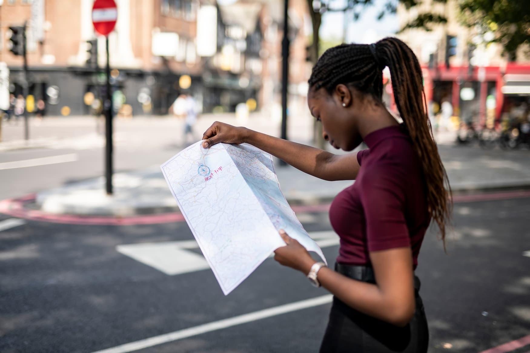 Schwarze Touristin liest Straßenkarte in London, da sie alleine reist