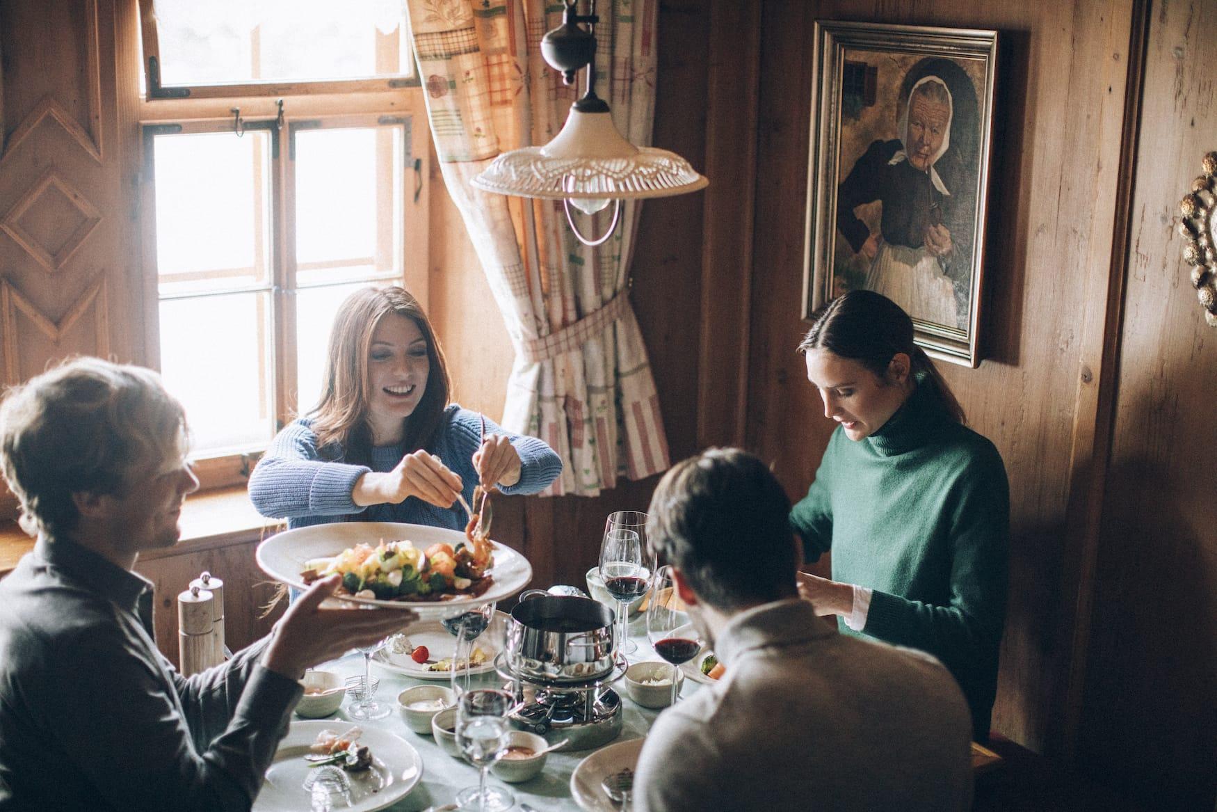 Vier Freunde sitzen bei geselligem Fondue-Abend im Hotel Arlberg