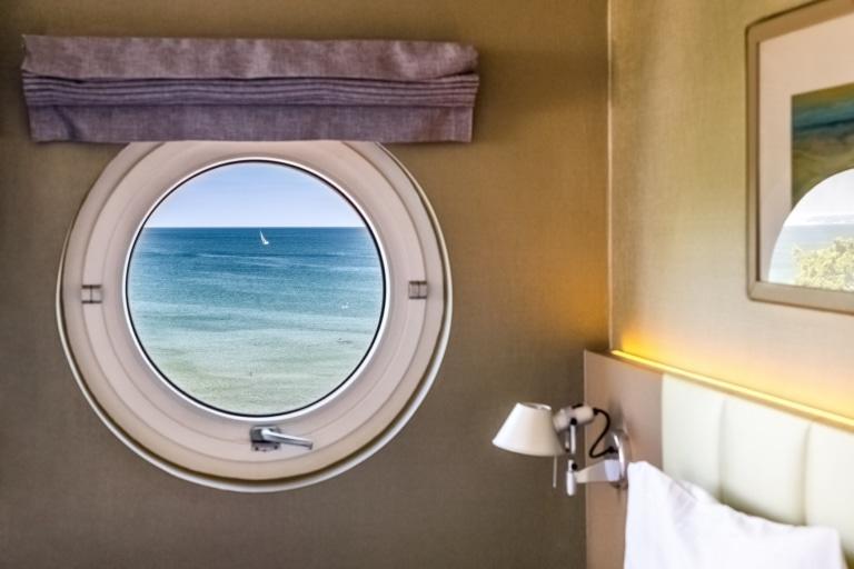 Schöner Aufwachen: Ostseeblick durch ein Bullauge im Hotel am Meer. | TMV/Tiemann