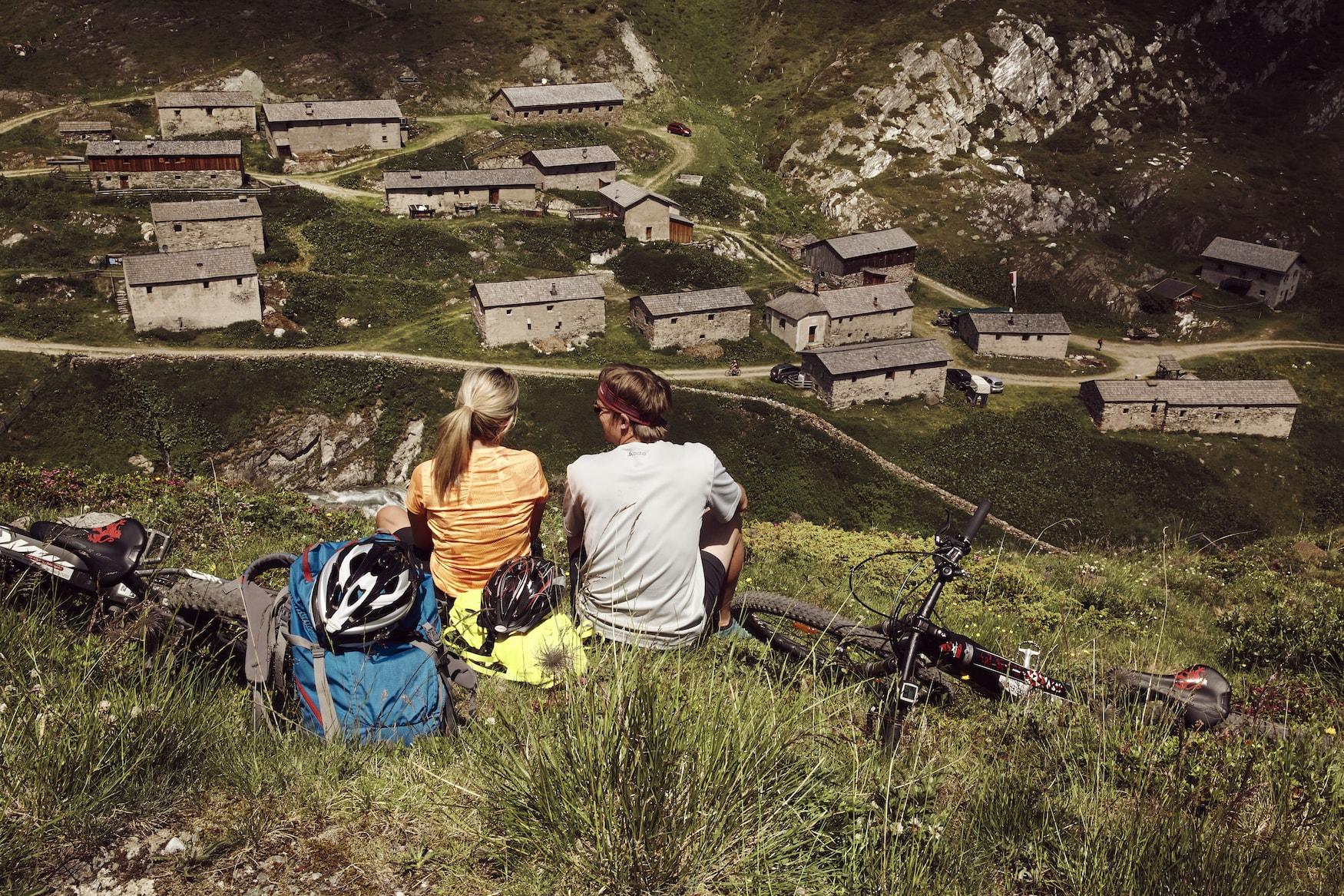 Pärchen sitzt mit Mountainbikes auf einem Aussichtspunkt im Nationalpark Hohe Tauern und genießt eine Sicht auf die österreichischen Alpen
