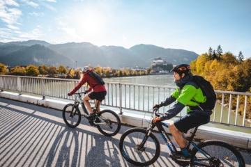 Fahrradfahrer fahren über Brücke in Kufstein mit Blick aufs Schloss