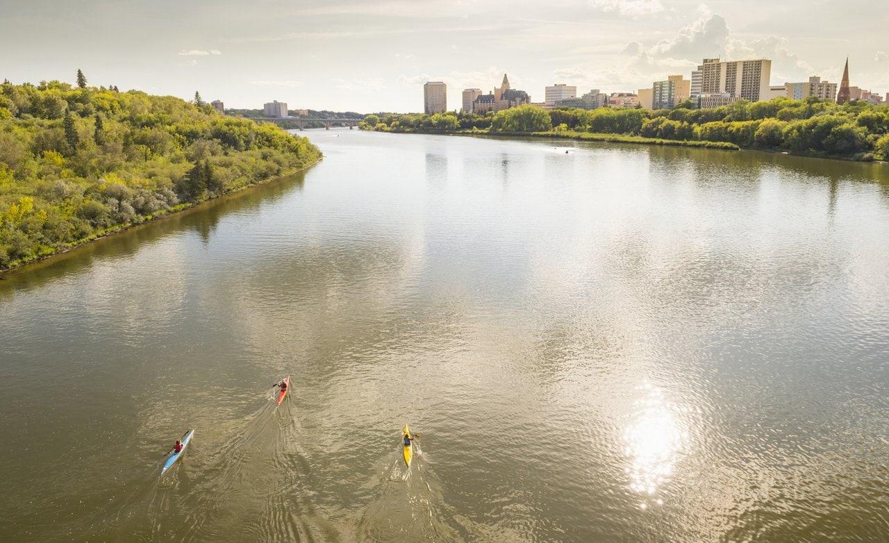 Kanufahrer auf einem Fluss mit der Skyline von Saskatoon im Hintergrund