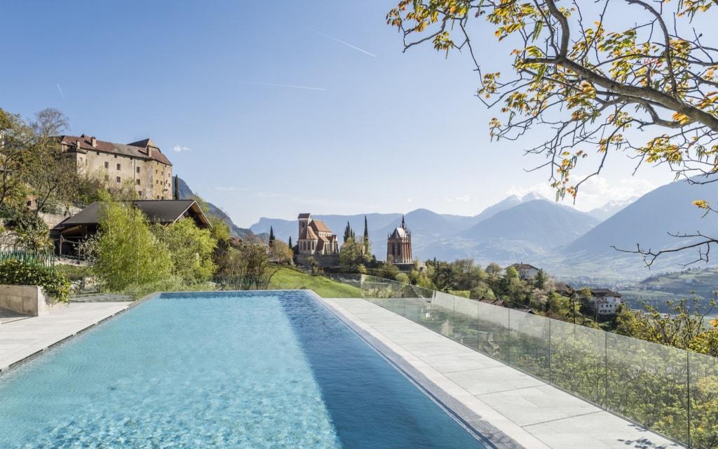 Blick über den Pool des Hotel Finkennest in Schenna mit Bergkulisse im Hintergrund