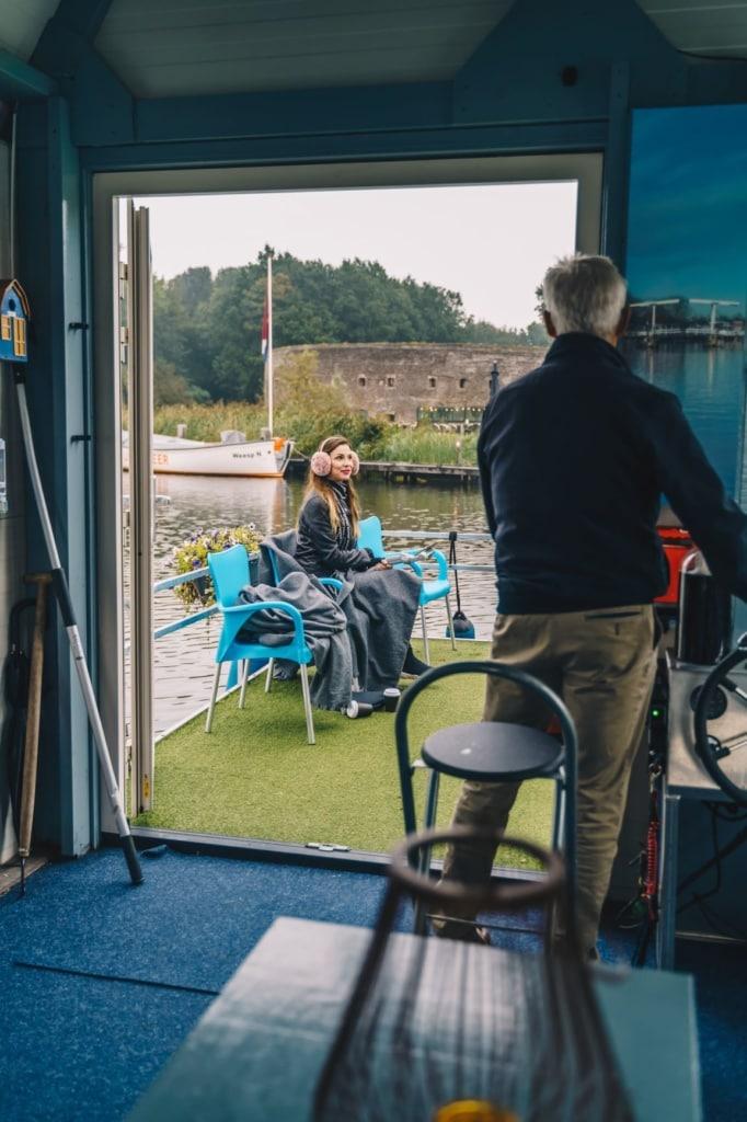 Kapitän und junge Frau während Bootstour auf dem Fluss Vecht in der Nähe von Amsterdam
