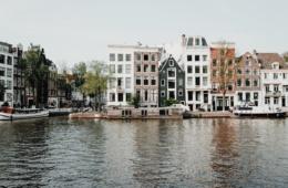 Schmale Häuser an Fluss in Amsterdam