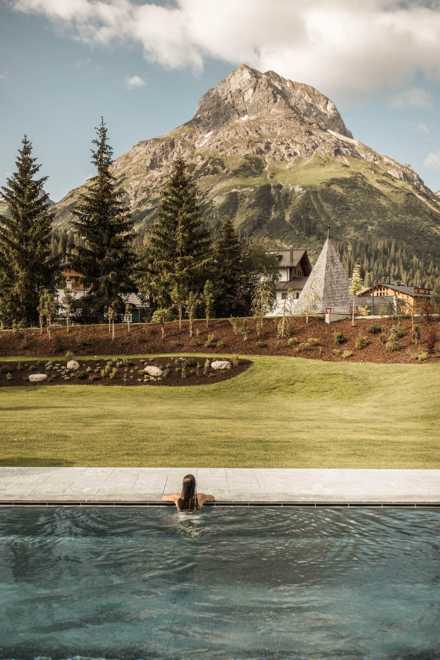 Hotelgast sitzt in Outdoor-Pool und blickt auf die umliegenden Berge im österreichischen Lech