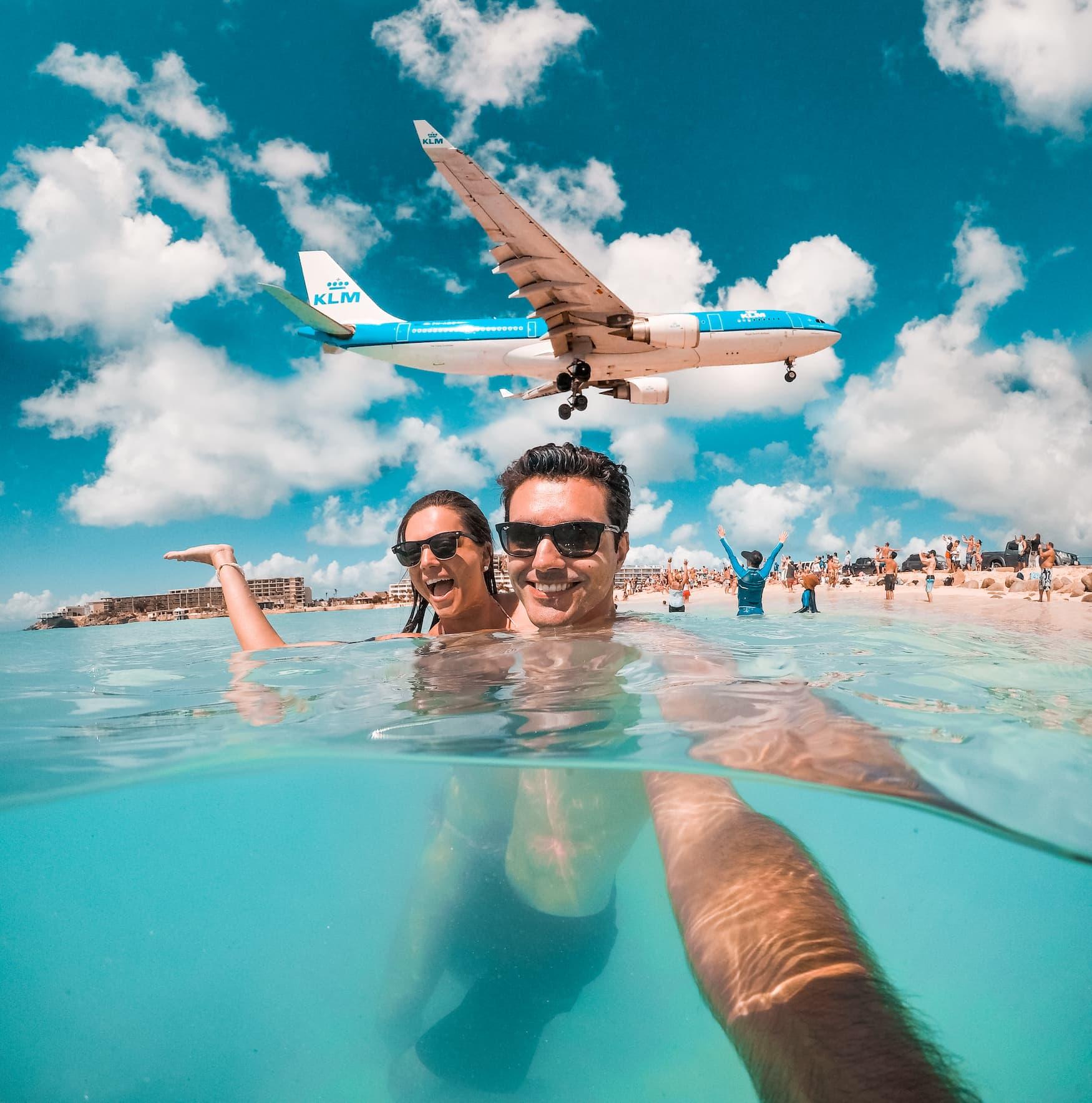Pärchen macht Selfie am Maho Beach in Sint Marteen, mit Flugzeug über den Köpfen