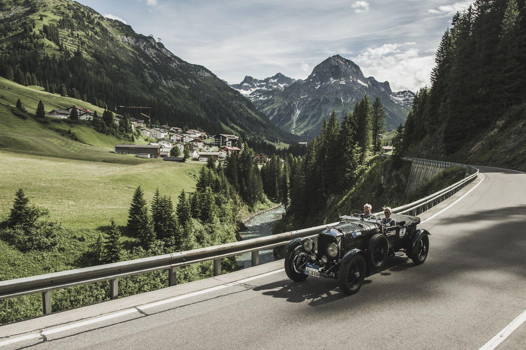 Älteres Pärchen unternimmt eine Fahrt mit einem Oldtimer durch die österreichischen Landschaften bei Lech
