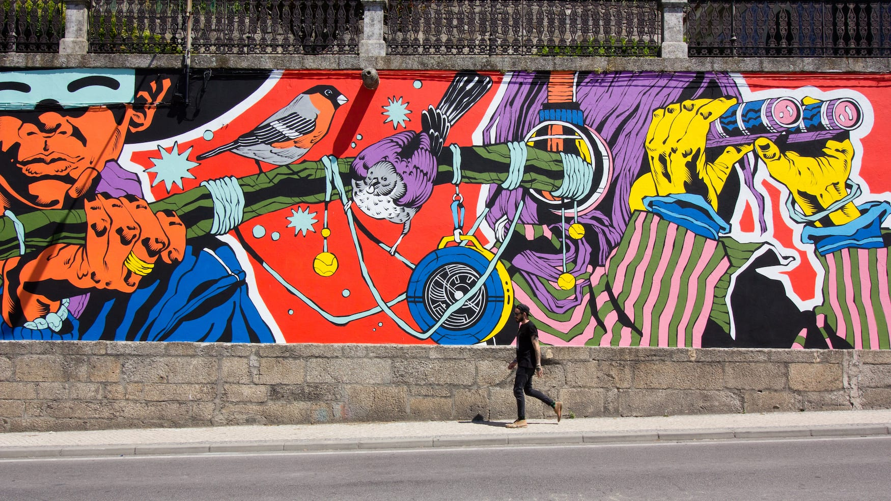 Mann spaziert vor bunter Graffiti-Hauswand entlang