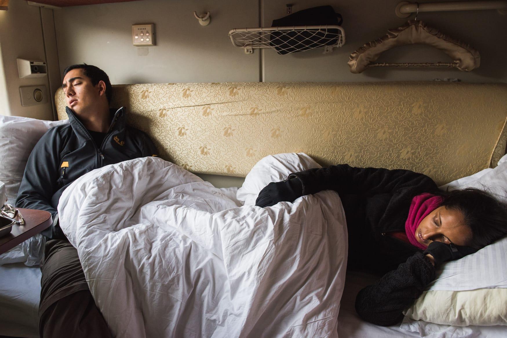 Frau und Mann erledigen Höhenkrankheit während einer Zugfahrt in Tibet