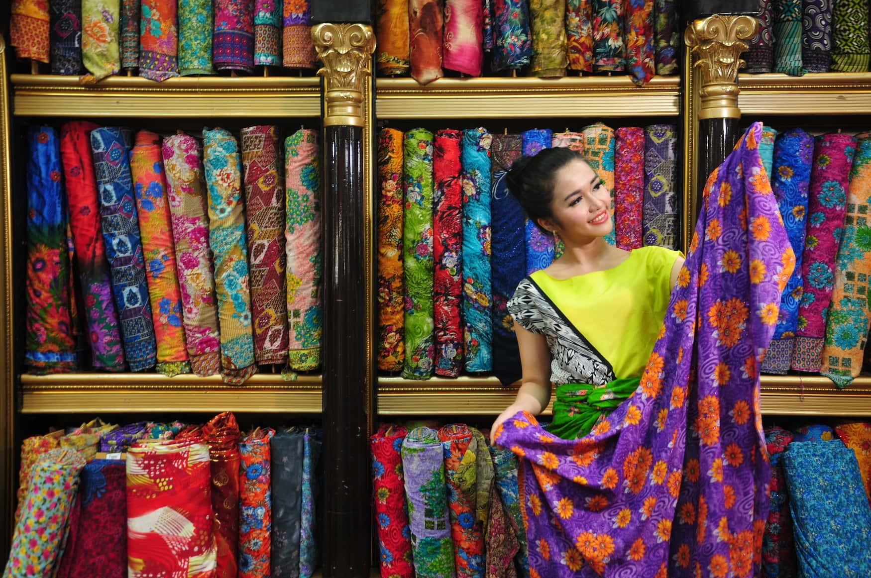 Junge Frau aus Indonesien hält Batiktuch in der Hand