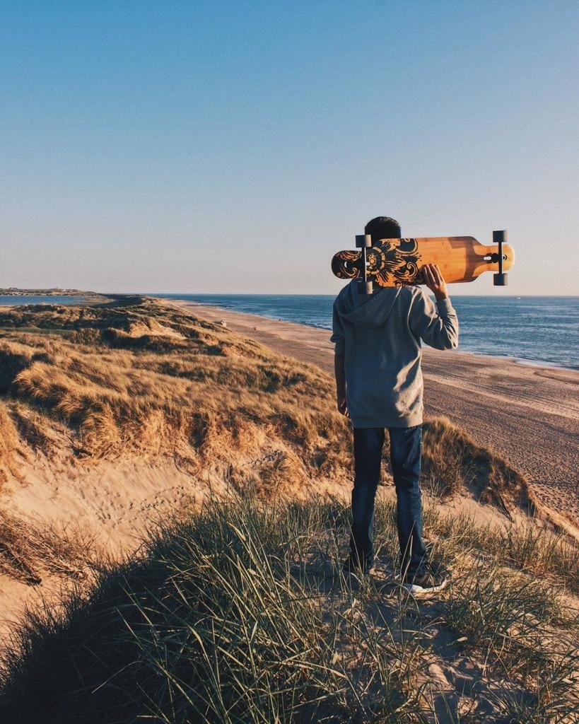 Mann mit Skateboard am Strand von Dänemark