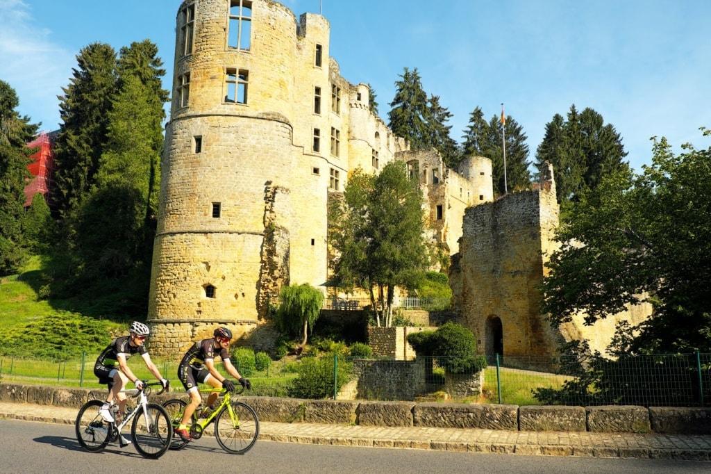 Radfahrer vor Schloss Beaufort in Luxemburg