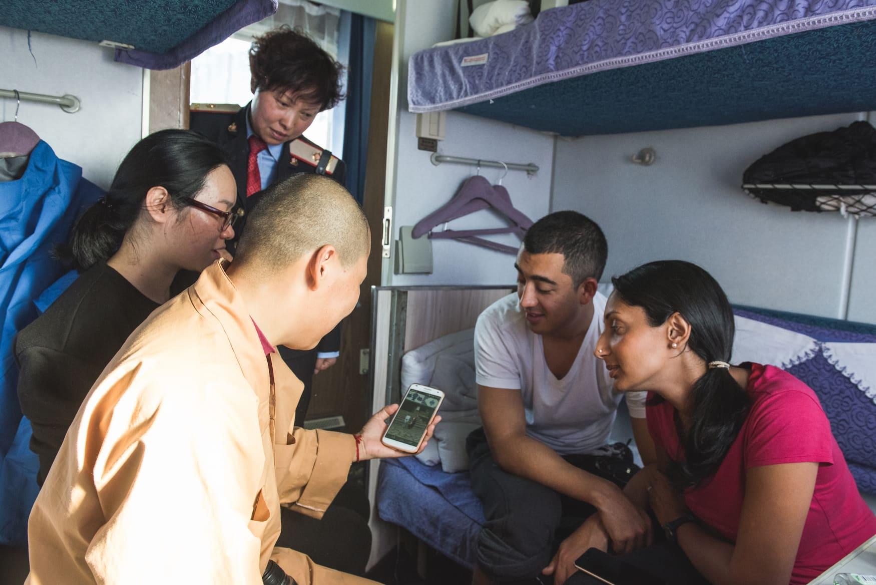 Einheimische sitzen in Zug in Tibet und zeigen sich Handyvideos