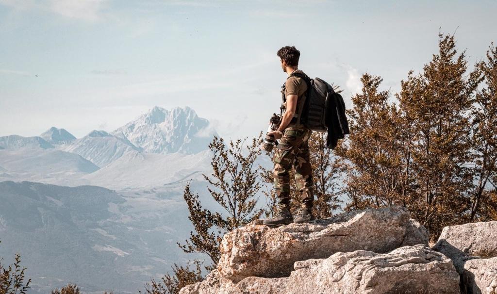 Fotograf steht auf einem Felsen und genießt die Aussicht über den Nationalpark Majella in den Abruzzen