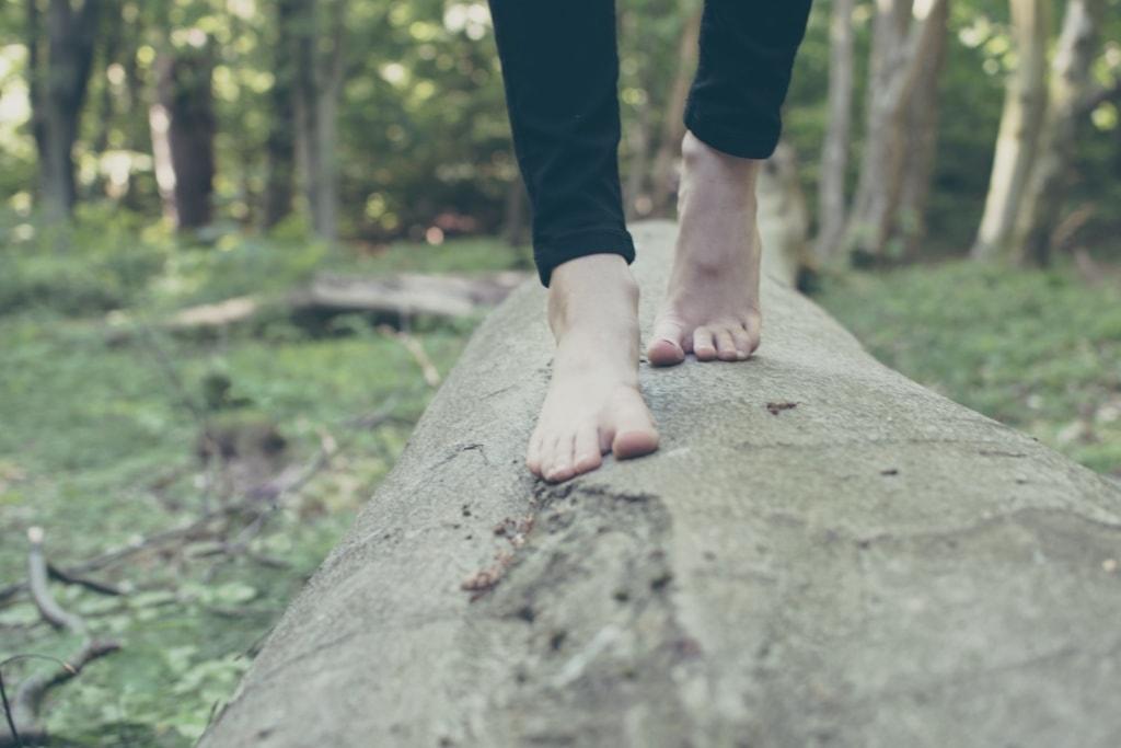 Füße gehen auf Baumstamm