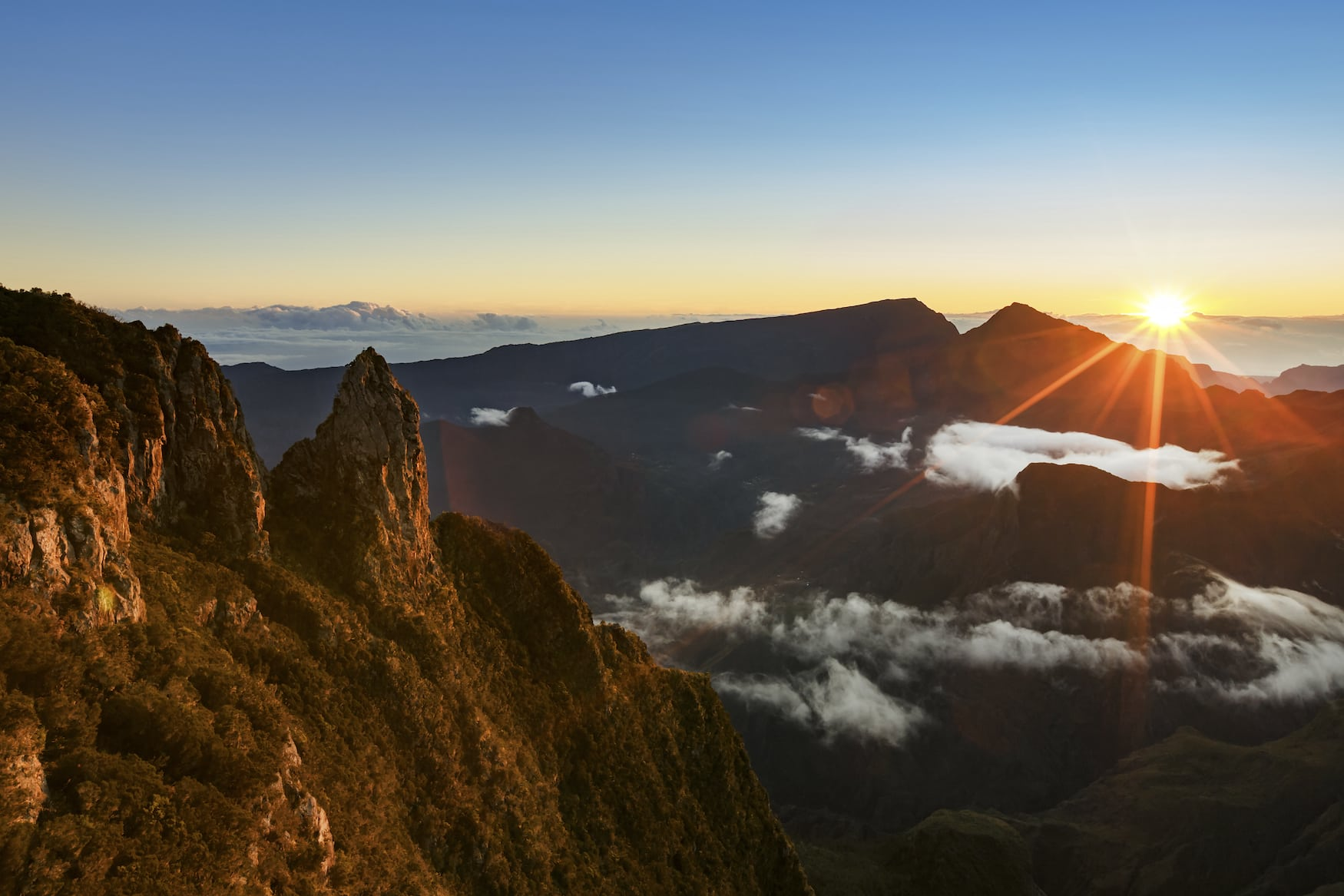 Sonnenaufgang über einem Gebirge auf La Réunion, wo es sich prima wandern lässt