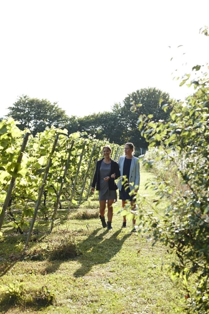Zwei Frauen laufen durch ein Weingut auf der Insel Fünen