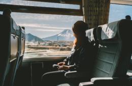 Junge Frau guckt aus dem Fenster während Zugfahrt in Japan