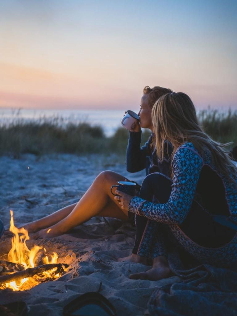 Zwei junge Frau sitzen an einem Lagerfeuer in Dänemark
