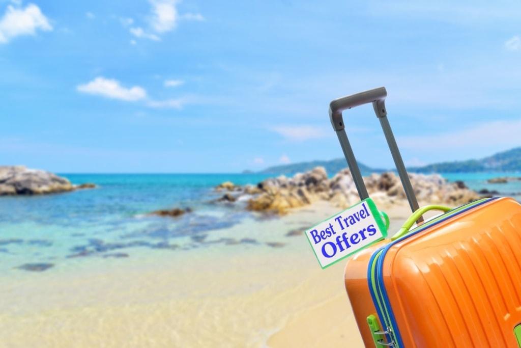 """Koffer mit Aufschrift """"Best Travel Offer"""" am Strand"""