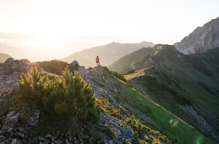 Wanderin läuft auf Grat, Berge im Hintergrund.
