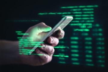 Online-Betrug: Person hält Handy in der Hand