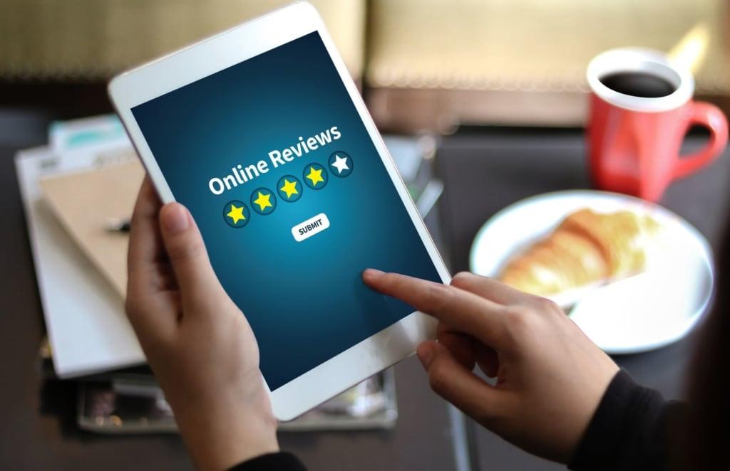 """Person hält Tablett in der Hand, auf dessen Display """"Online Reviews"""" steht"""