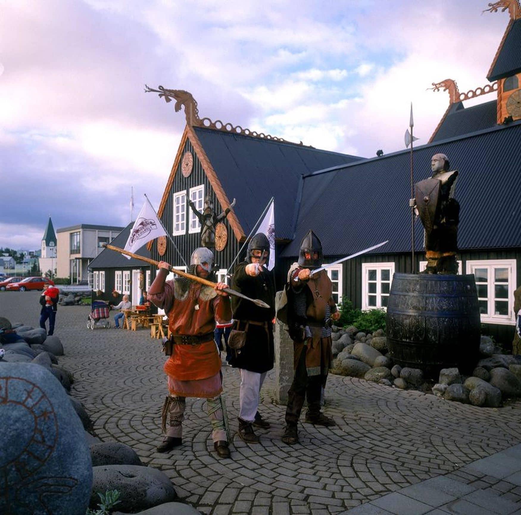 Menschen stehen als Wikinger verkleidet vor einem Wikingerhotel