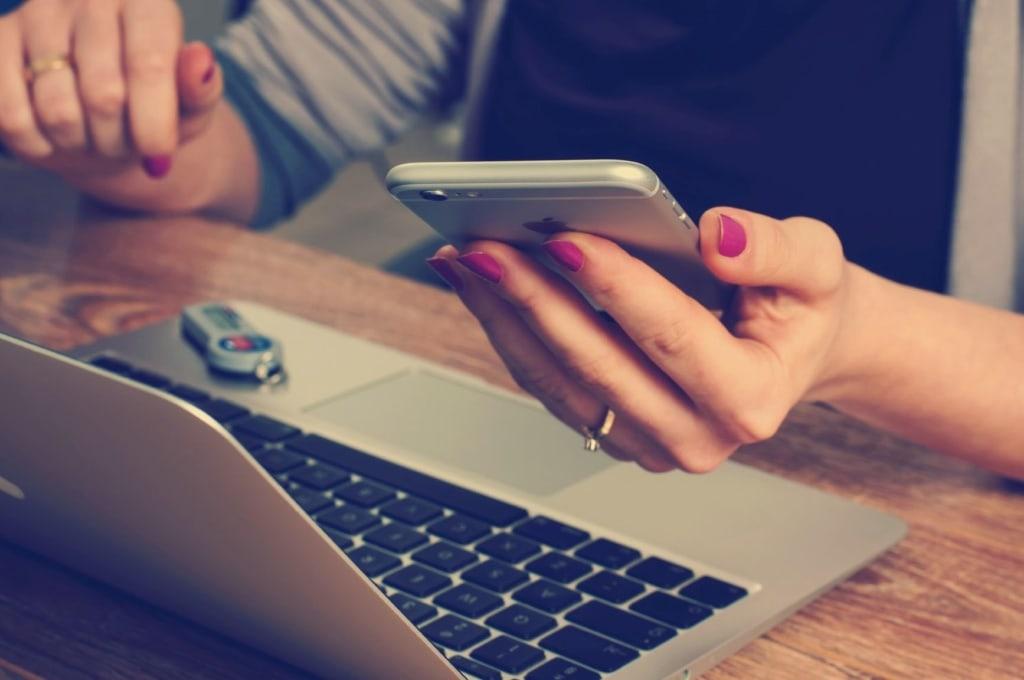 Frau sitzt vor Notebook und hält Apple-Handy in der Hand