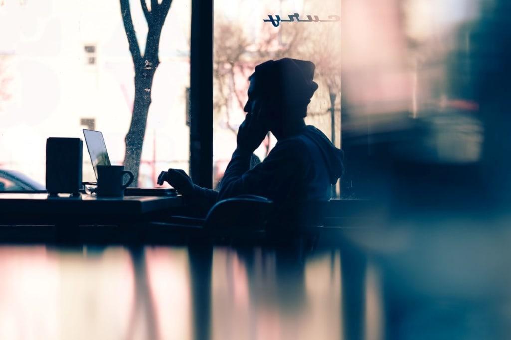 Mann sitzt im Kaffee vor Notebook