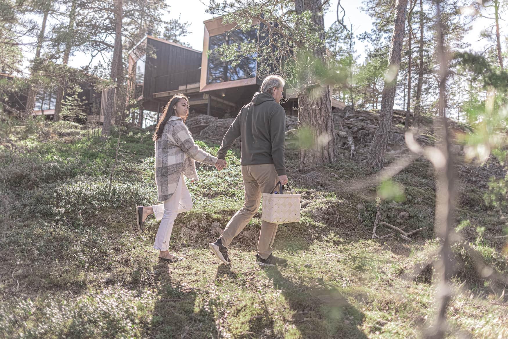 Mann und Frau spazieren durch Natur in Finnland, im Hintergrund sieht man ihr Hotel