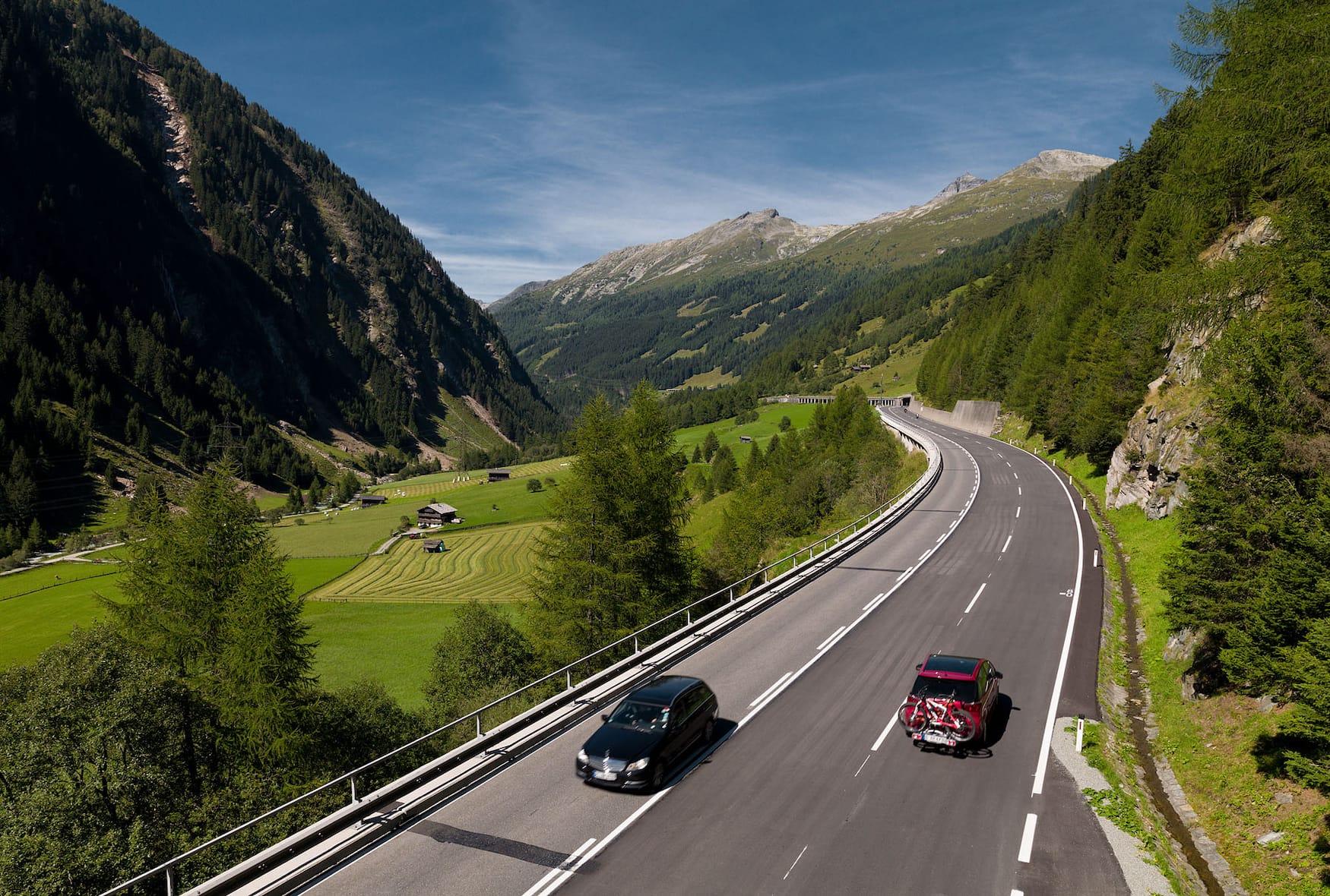 Autos fahren auf der Felbertauernstraße zwischen Bergpanorama der Alpen