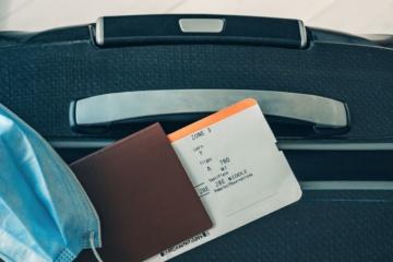 Koffer, auf dem Reisepass, Flugticket und Mund-Nasen-Schutz-Maske liegen
