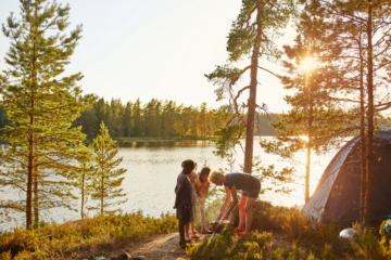 Familie campt an Flussufer in Schweden