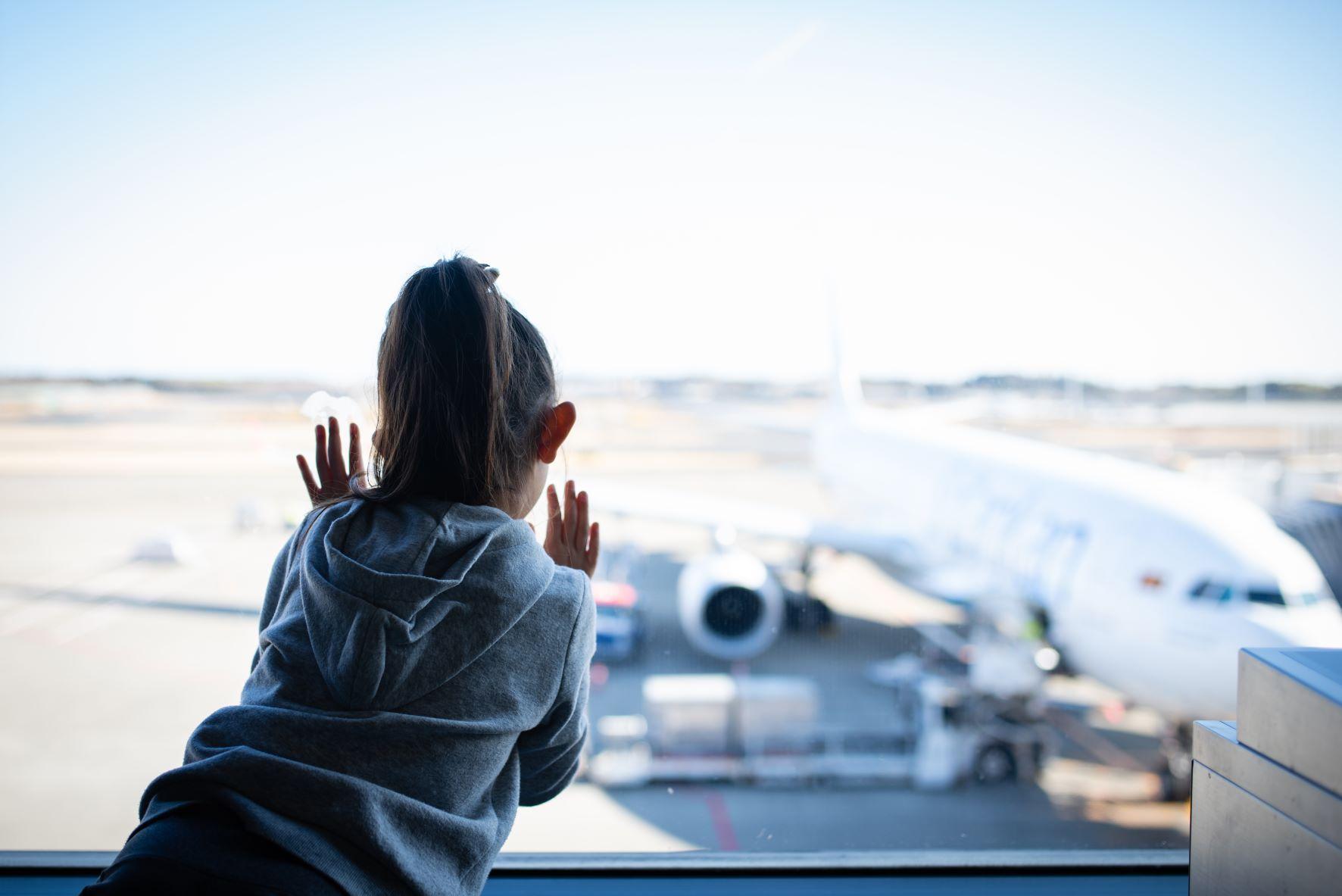 Mädchen blickt im Flughafen am Fenster auf Rollfeld