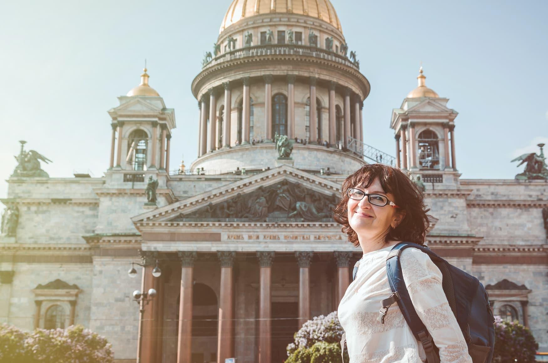 Glückliche Frau vor einer Kirche in St. Petersburg