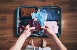 Mann hält Reisepass, Desinfektionsflasche und Corona-Schutzmasken in seinen Händen, vor im auf dem Boden ein gepackter Urlaubskoffer