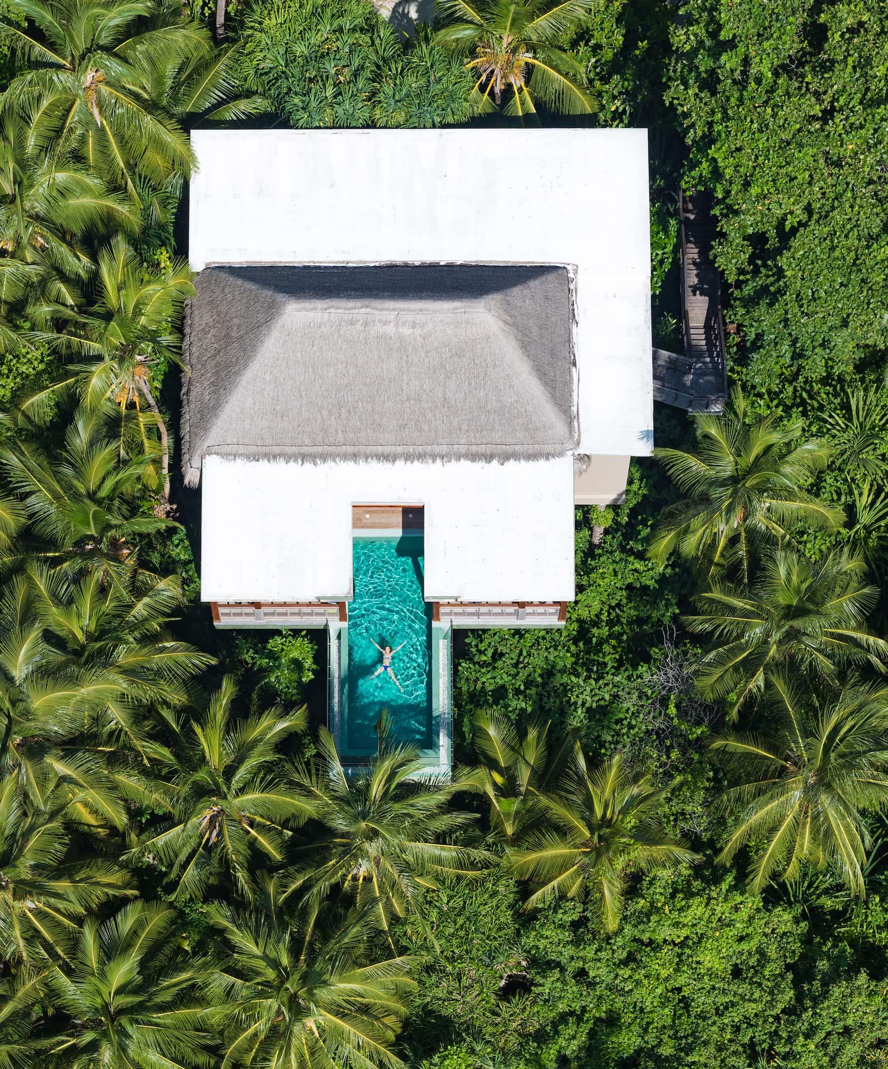 Frau schwimmt in Pool in der Tree House Villa des Amilla Fushi
