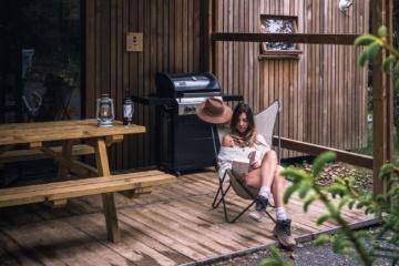 Frau sitzt vor Holzhütte im Wald und liest ein Buch